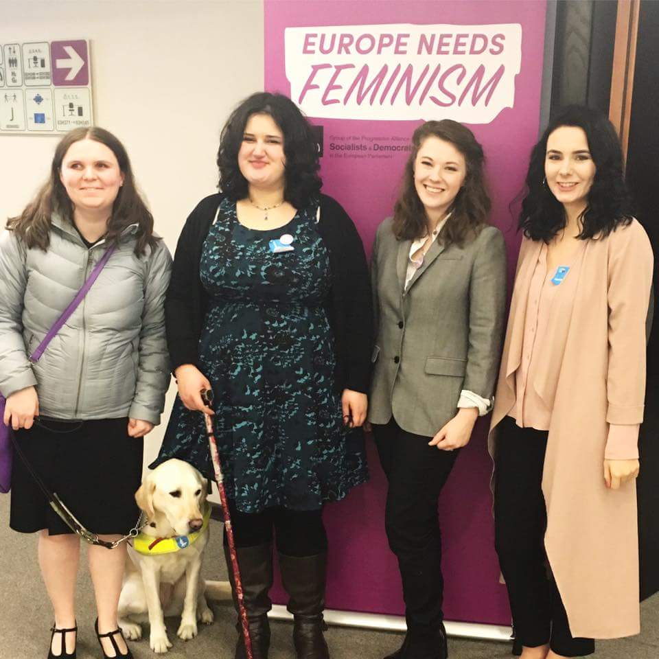 Holly and guide dog Isla with DSU co-founders Alice, Ashley and Bekki in front of Europe Needs Feminism sign